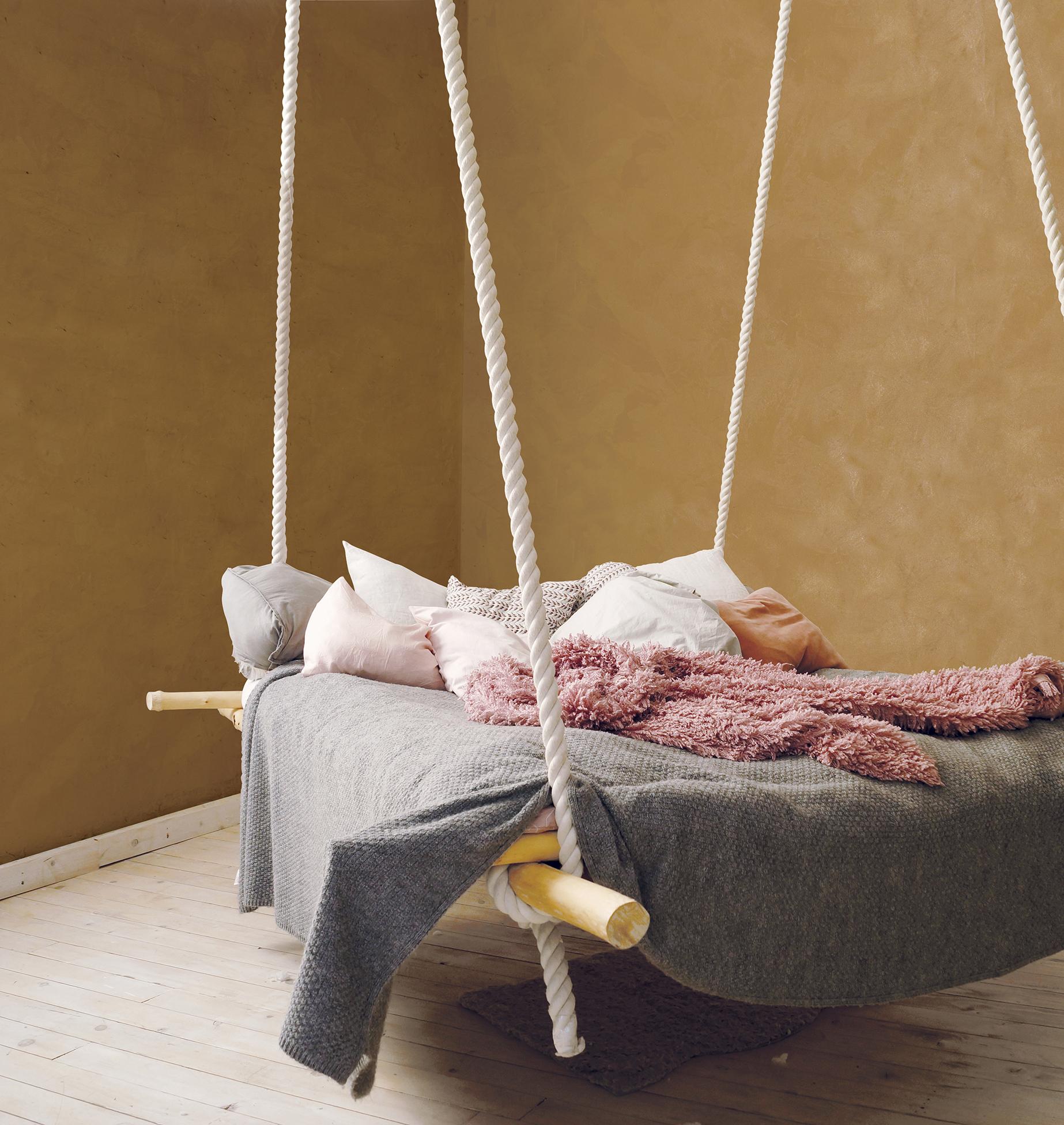 Hanging bed in rural or loft bedroom interior.